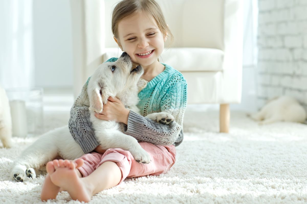 Portrait,Of,Happy,Little,Girl,At,Home,With,Labrador,Puppy